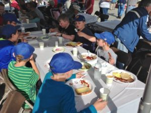 children eating breakfast under tent