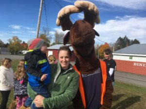Maine Highlands employee with child posing with Monty Moose
