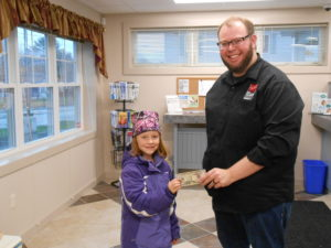 employee handing prize to young girl