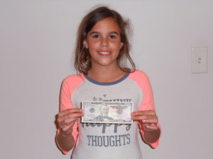 young girl holding cash prize