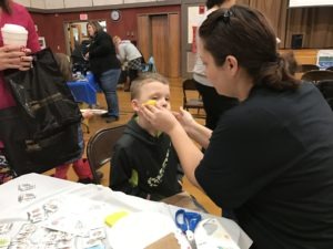 boy getting his face painted at event