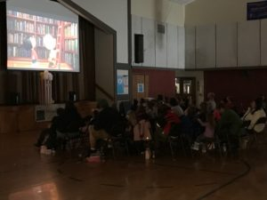 children and adults watching Charlie Brown movie in a gymnasium