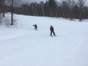 two boys skiing down mountain