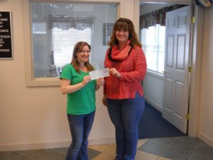 employee presenting check to member
