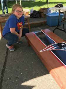 young girl posing in front of New England Patriots cornhole game that she won