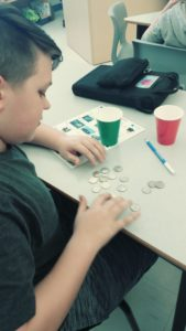 boy in classroom counting coins