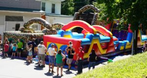 inflatable obstacle courses and several people waiting their turn to use them