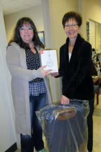 Second place winner holding headphones and luggage with Dexter employee