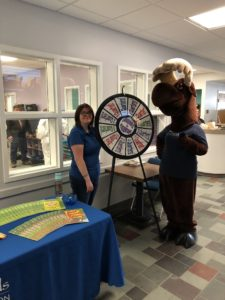 employee posing with Monty Moose at prize wheel