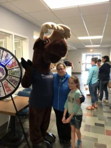Monty Moose with employee and young girl