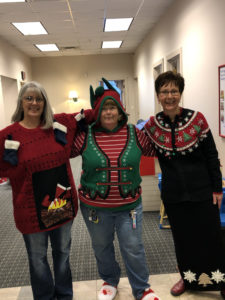 employees in ugly Christmas sweaters