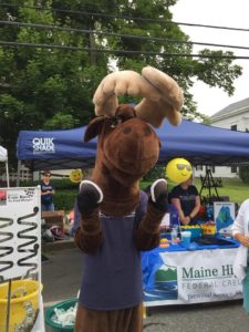 Monty Moose at festival holding two whoopie pies