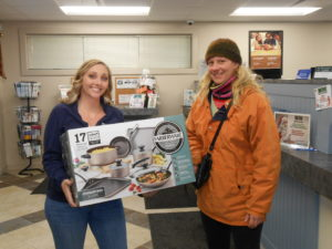 Third place winner holding set of cookware with Greenville employee