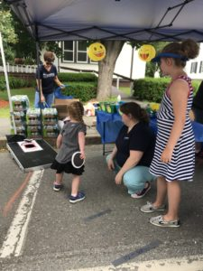 child playing bean bag toss game at festival