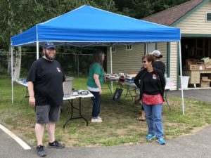employees ready to help with yard sale at canopy with yard sale items