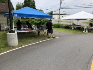 Two canopies set up with yard sale items and several employee volunteers