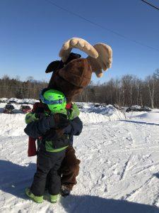 Monty Moose hugging young skiier