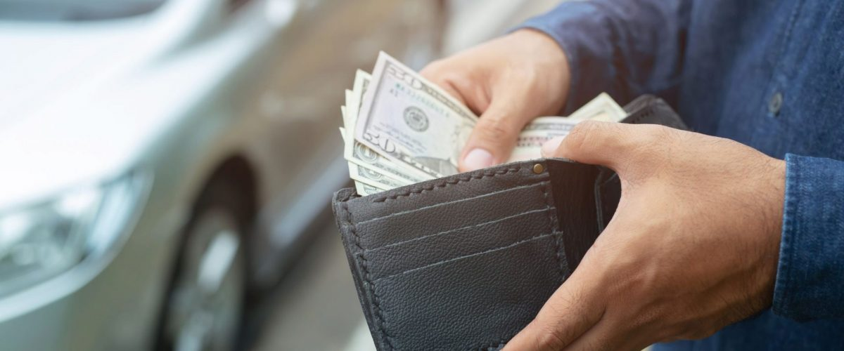 man putting cash in his wallet