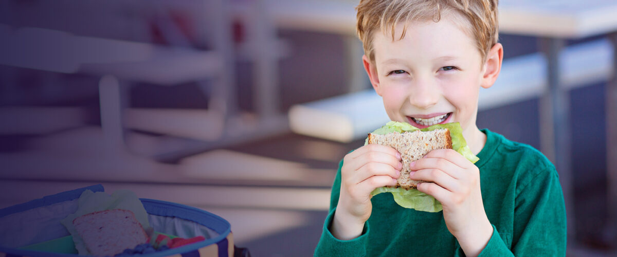 young boy eating a sandwich