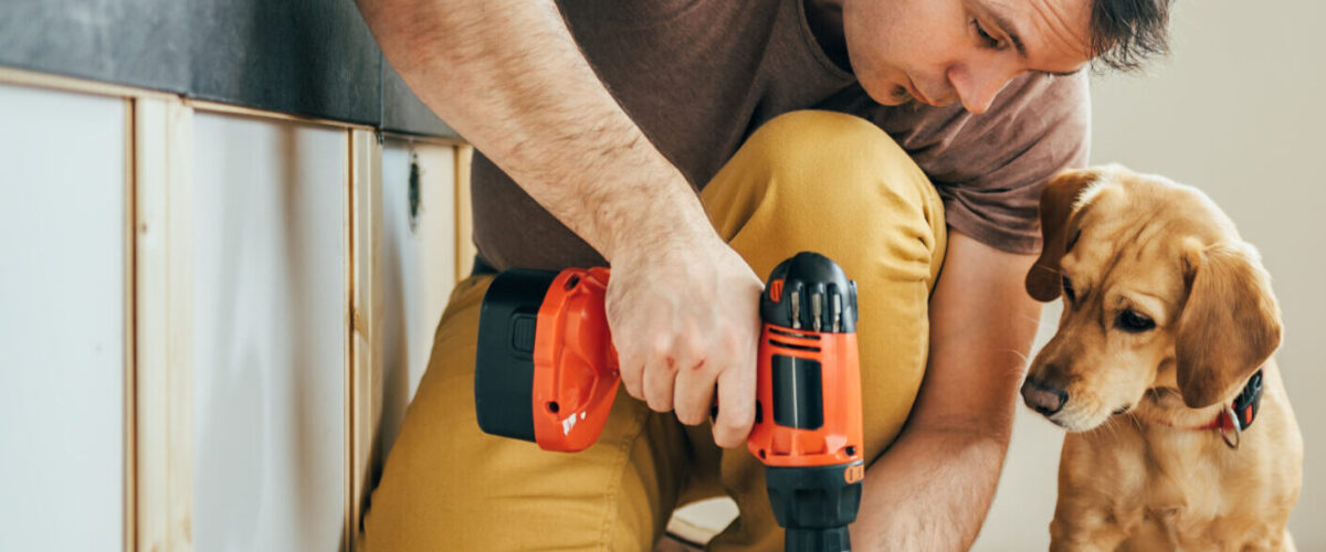 man using screwdriver while dog looks on